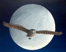 An owl flying infront of the moon