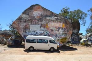 Van in front of rock